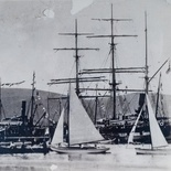 Knysna Yacht Club yachts and pulling boat pass the ss Agnar, ss Ingerid, and one of the whalers from Plettenberg Bay at Thesens Wharf, early 20th Century