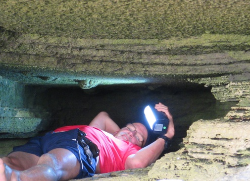 Charles W. Helm, a discoverer of the fossil hominin footprint tracksite near Knysna, South Africa, works in the confined space at the rear of the cave. Image: Linda Helm
