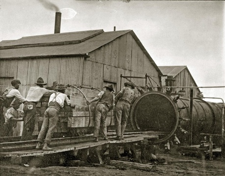 Loading the treatment kilns in the government sleeper factory. Woodcutters of the Knysna Forests
